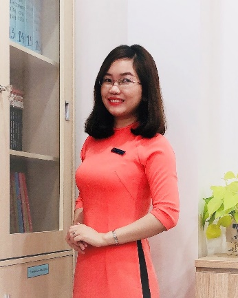 A person in a red dress standing in a room Description automatically generated